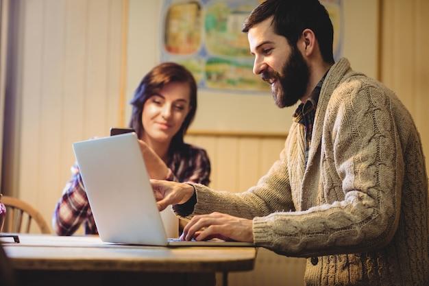 Pareja interactuando mientras usa una computadora portátil y un teléfono móvil