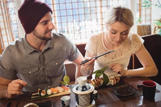 Pareja interactuando entre sí mientras toma sushi