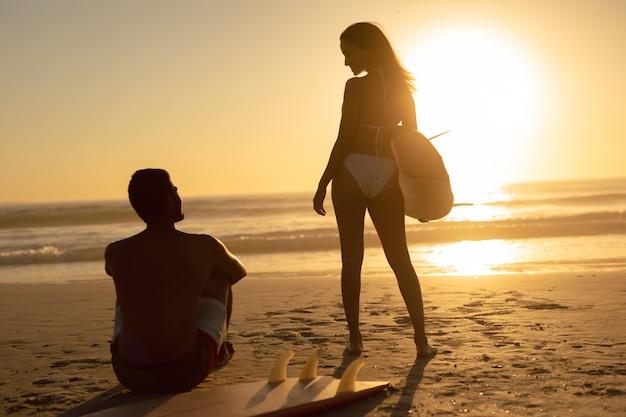 Pareja interactuando entre sí en la playa durante el atardecer