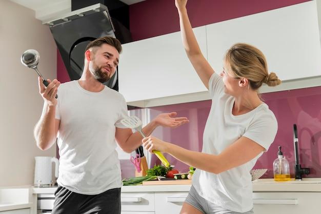 Pareja en el interior bailando en la cocina tiro medio