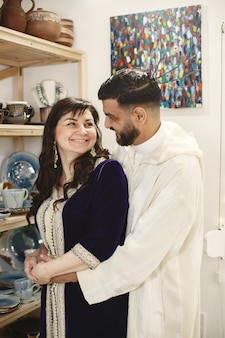 Pareja internacional. pareja elegante adulta en casa. personas de pie junto al estante con utensilios.