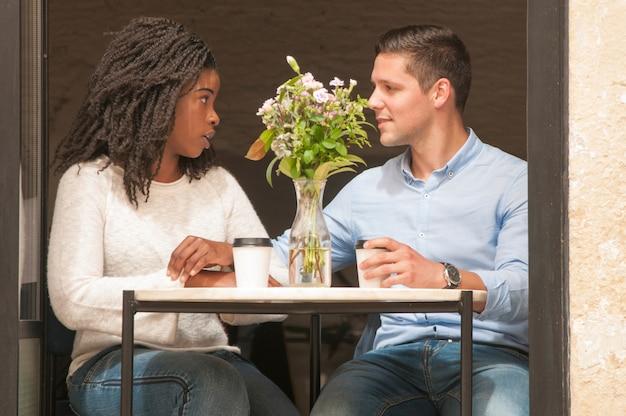 Pareja interracial discutiendo en cafe