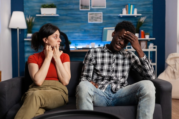 Pareja interracial discutiendo sentado en el sofá