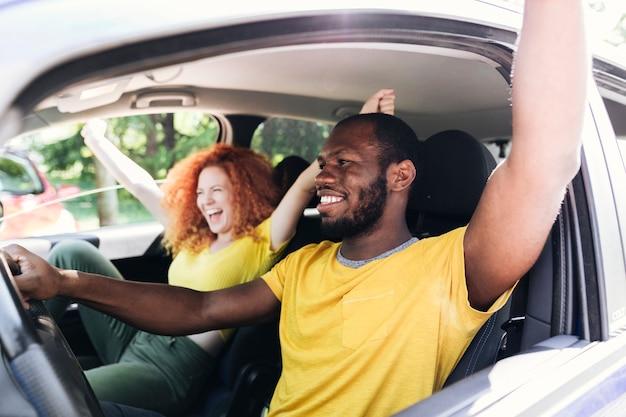 Pareja interracial divirtiéndose en un viaje en coche