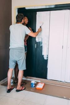 Pareja interracial pintando un armario