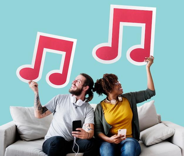 Pareja interracial en un sofá con notas musicales
