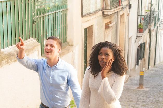 Pareja interracial de turistas entusiasmados con hitos.