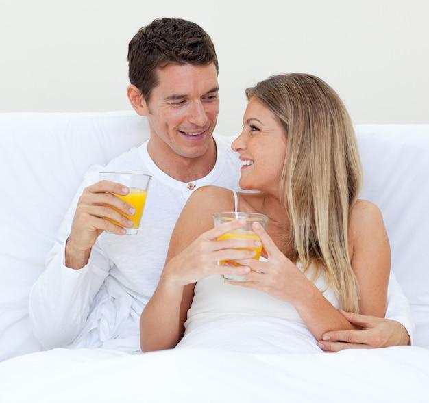 Pareja íntima bebiendo jugo de naranja acostado en su cama
