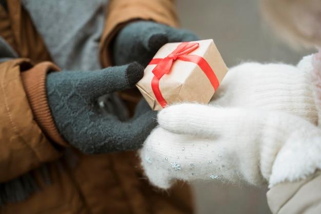 Pareja en invierno dando y recibiendo regalos