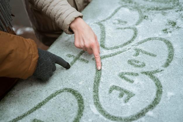 Pareja en invierno escribiendo amor con corazón en la nieve.