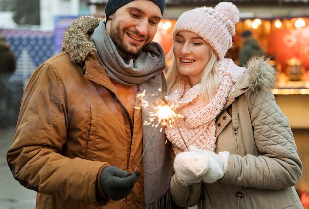 Pareja en invierno mujer sosteniendo destellos de fuegos artificiales