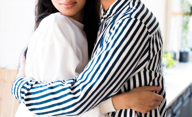 Pareja irreconocible en el amor abrazando suavemente juntos