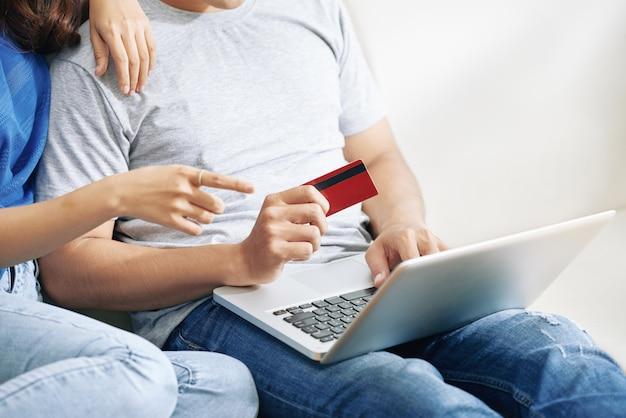 Pareja irreconocible sentado en el sofá con laptop y hombre con tarjeta de crédito
