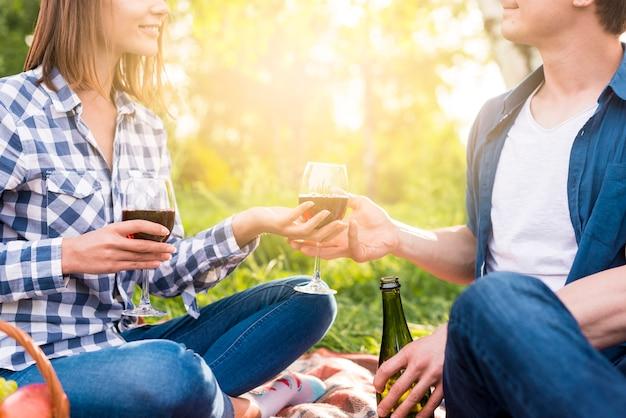 Pareja irreconocible teniendo momento romántico fuera con vino