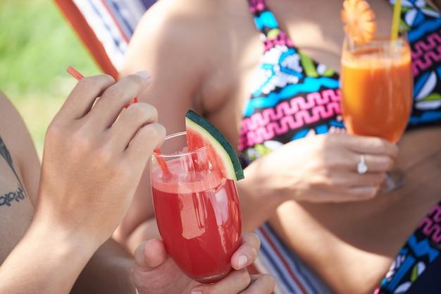 Pareja irreconocible en trajes de baño disfrutando de bebidas en lujoso resort