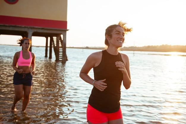 Pareja de jogger mujer corriendo en el agua