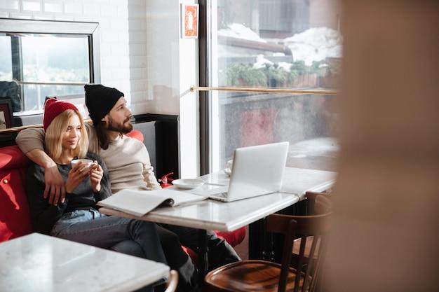 Pareja joven abrazando y sentado en la cafetería