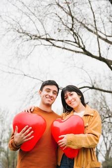 Pareja joven abrazando y sosteniendo globos en forma de corazón