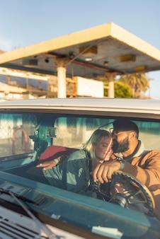 Pareja joven abrazándose en el coche antes de su viaje