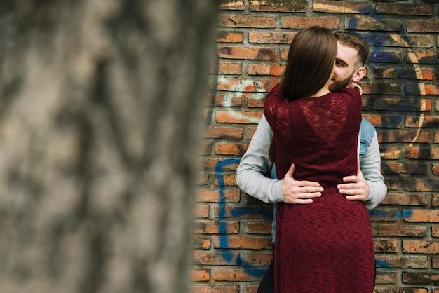 Pareja joven abrazándose enfrente de pared de ladrillo
