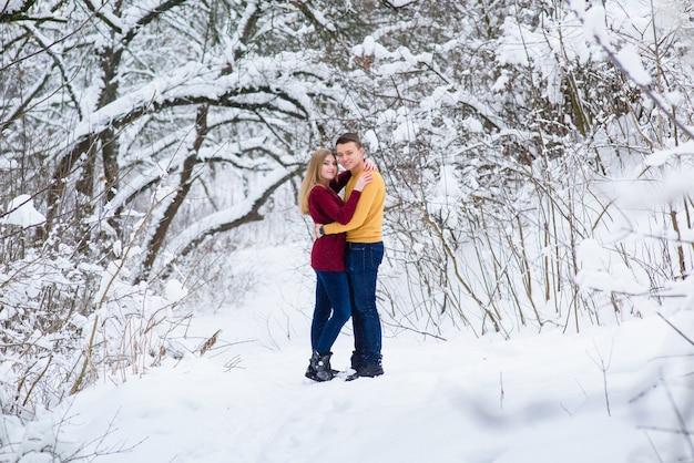 Pareja joven abrazo en bosque de invierno
