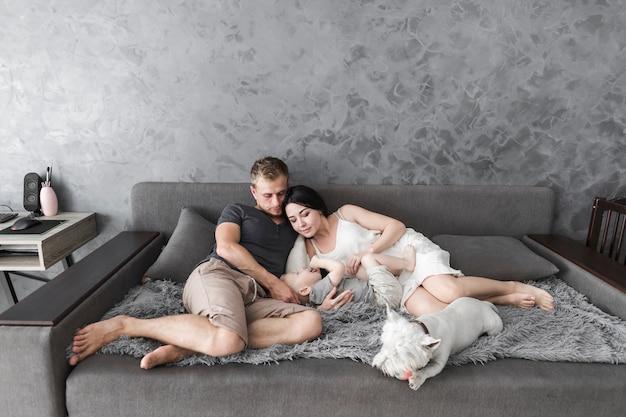 Pareja joven acostado con su lindo hijo y perro en sofá