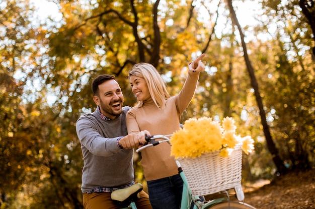 Pareja joven activa disfrutando juntos en bicicleta en el parque otoño dorado