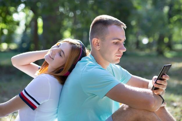 Pareja joven adolescente divirtiéndose al aire libre en el parque de verano. chica con el pelo rojo escuchando música en auriculares rosa y chico chateando en el teléfono de venta.