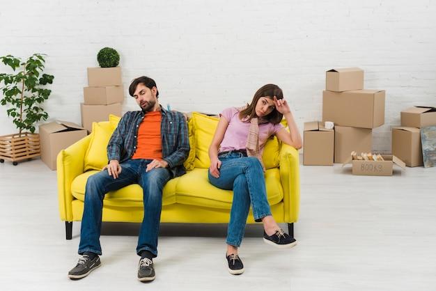 Pareja joven agotada sentada en un sofá amarillo con cajas de cartón en movimiento en su nuevo hogar