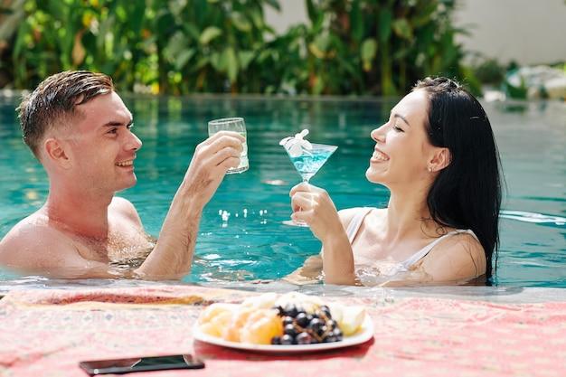 Pareja joven alegre chapoteando en agua y bebiendo deliciosos cócteles