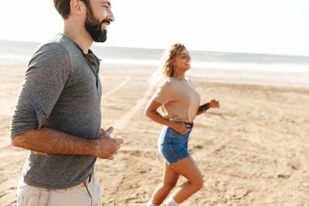 Pareja joven alegre corriendo en la playa soleada