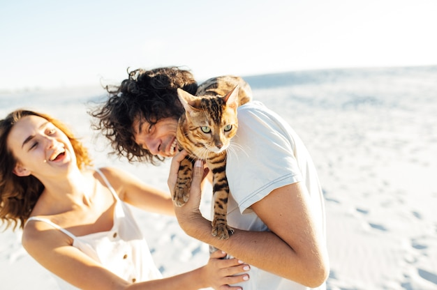 Pareja joven alegre divirtiéndose en la playa con su gato de bengala.
