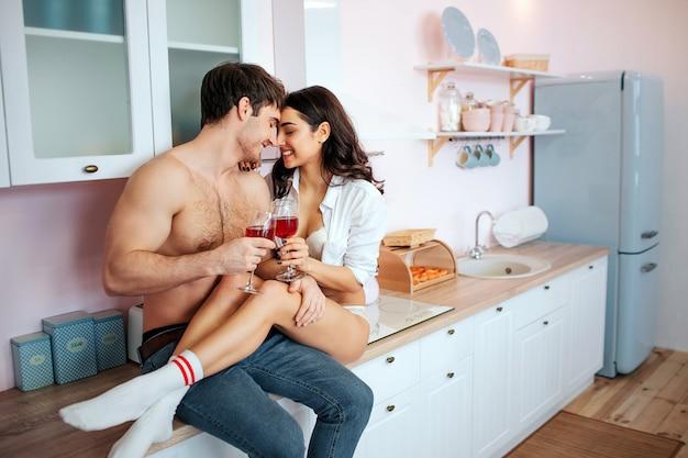 Pareja joven alegre y feliz en la cocina. se sientan en el armario de la cocina y sonríen. la gente tiene copas de vino tinto en las manos.