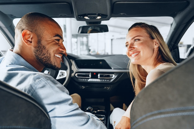 Pareja joven alegre mirando dentro de un coche nuevo que van a comprar en una tienda de coches