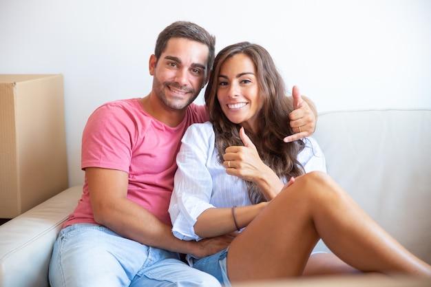 Pareja joven alegre posando en el sofá cerca de la caja de cartón, mostrando gestos similares o telefónicos