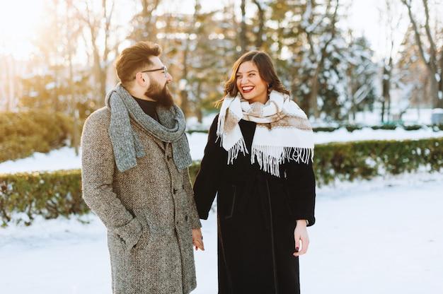 Pareja joven alegre riendo mirando el uno al otro en el parque en invierno.