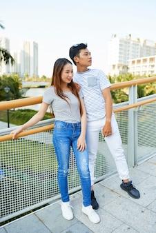Pareja joven alegre en ropa casual de pie en el puente