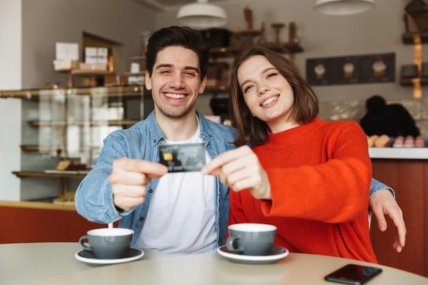 Pareja joven alegre sentado en una mesa de café