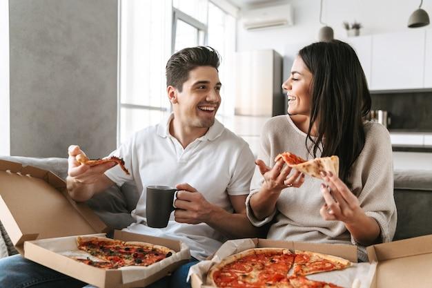 Pareja joven alegre sentado en un sofá en casa, comiendo pizza