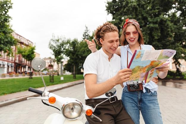 Pareja joven alegre sentados juntos en moto en la calle de la ciudad, analizando el mapa guía de la ciudad