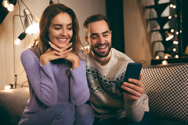 Pareja joven alegre sentados juntos en un sofá en casa, tomando un selfie