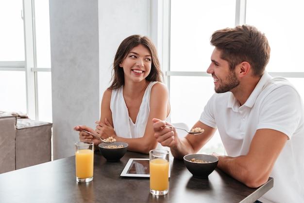 Pareja joven alegre con tableta bebiendo jugo y comiendo cereales para el desayuno en casa
