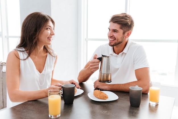 Pareja joven alegre tomando café con croissants en la cocina
