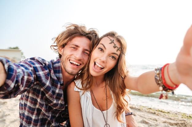 Pareja joven alegre tomando selfie y riendo en la playa
