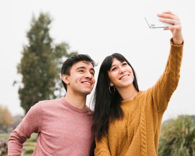 Pareja joven alegre tomando selfie con smartphone