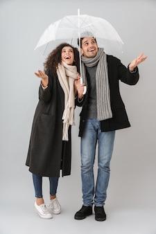 Pareja joven alegre vistiendo suéteres y bufandas aislado sobre pared gris, de pie bajo un paraguas