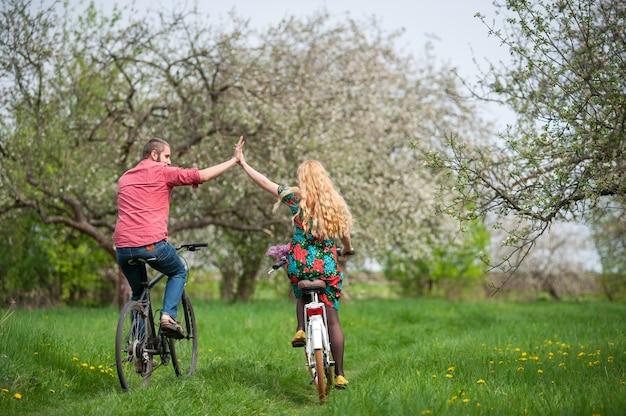 Pareja joven amante de andar en bicicleta en el jardín de primavera