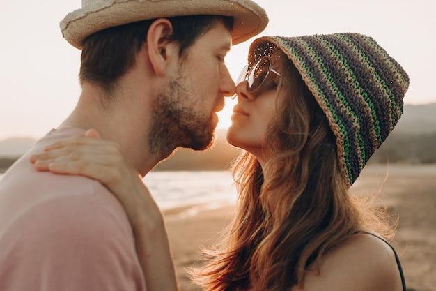 Pareja joven en el amor de pie en la playa, disfrutando de la puesta de sol del océano.