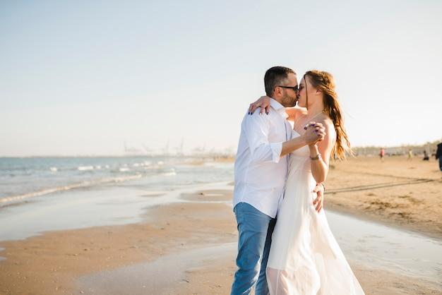 Pareja joven amorosa cogidos de la mano unos a otros besándose en la playa de verano