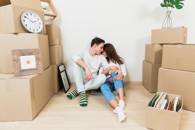 Pareja joven amorosa sentada entre la pila de cajas de cartón en su nuevo apartamento